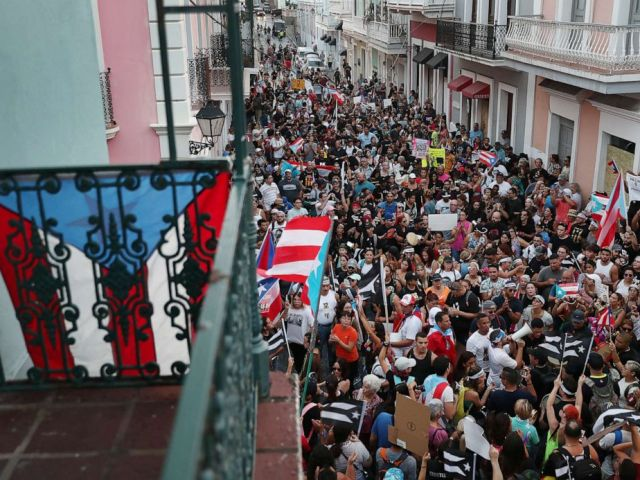 PHOTO: Protesters demonstrate against Ricardo Rossello, the Governor of Puerto Rico, near police that were manning a barricade set up along a street leading to the governors mansion on July 20, 2019, in Old San Juan, Puerto Rico.