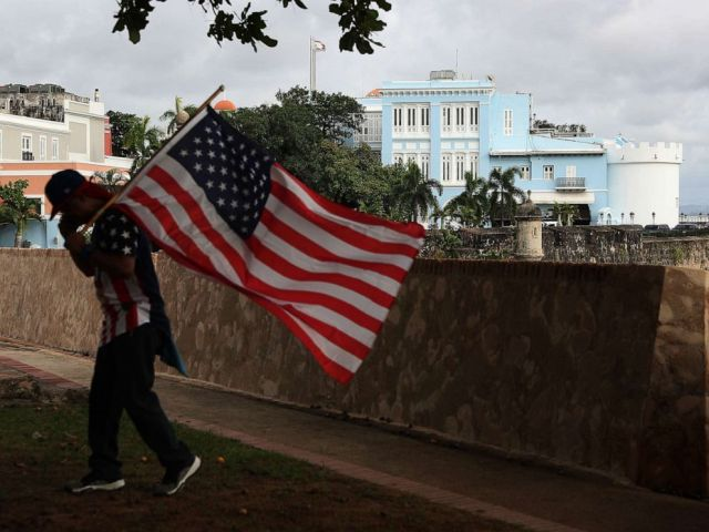 PHOTO: A man carrying a U.S. flag walks past the governors mansion where Ricardo Rossello, the Governor of Puerto Rico lives in Old San Juan, Puerto Rico, Aug. 1, 2019.