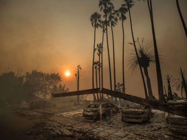Smoke rises behind a leveled apartment complex as a wildfire burns in Ventura, Calif., Dec. 5, 2017. Over 100 structures have burned so far in Ventura County, officials said.