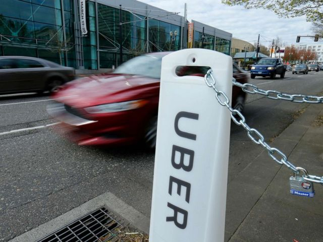 PHOTO: An Uber sign points to drop off and pick up location on a city street in Portland, March 19, 2016.