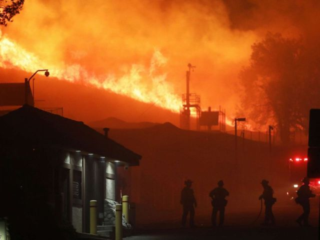PHOTO: Firefighters work as the Saddleridge Fire burns in the early morning hours on Oct. 11, 2019, in Porter Ranch, Calif.