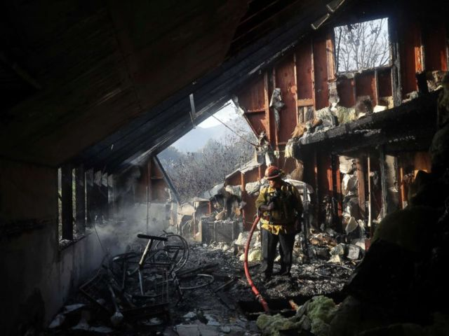 PHOTO: Capt. Adrian Murrieta with the Los Angeles County Fire Dept., looks for hot spots on a wildfire-ravaged home, Nov. 10, 2018, in Malibu, Calif.