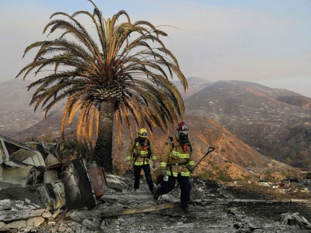 PHOTO: Firefighters Jason Toole, right, and Brent McGill with the Santa Barbara Fire Dept. walk among the ashes of a wildfire-ravaged home after turning off an open gas line, Nov. 10, 2018, in Malibu, Calif.