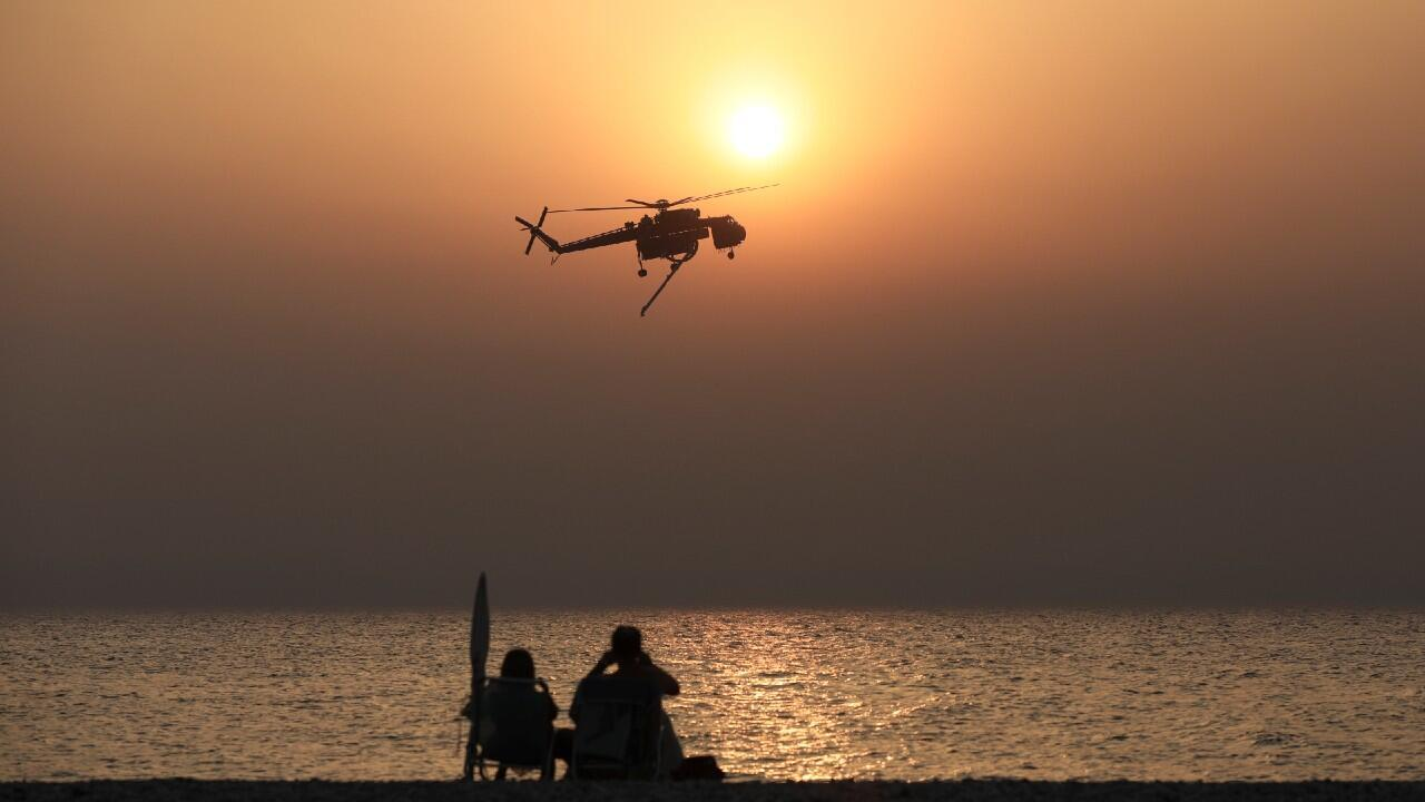 Bathers watch a firefighting helicopter as it prepares for a water recharge on the beach in the village of Pefki, on the island of Euboea, Greece, on August 10, 2021.