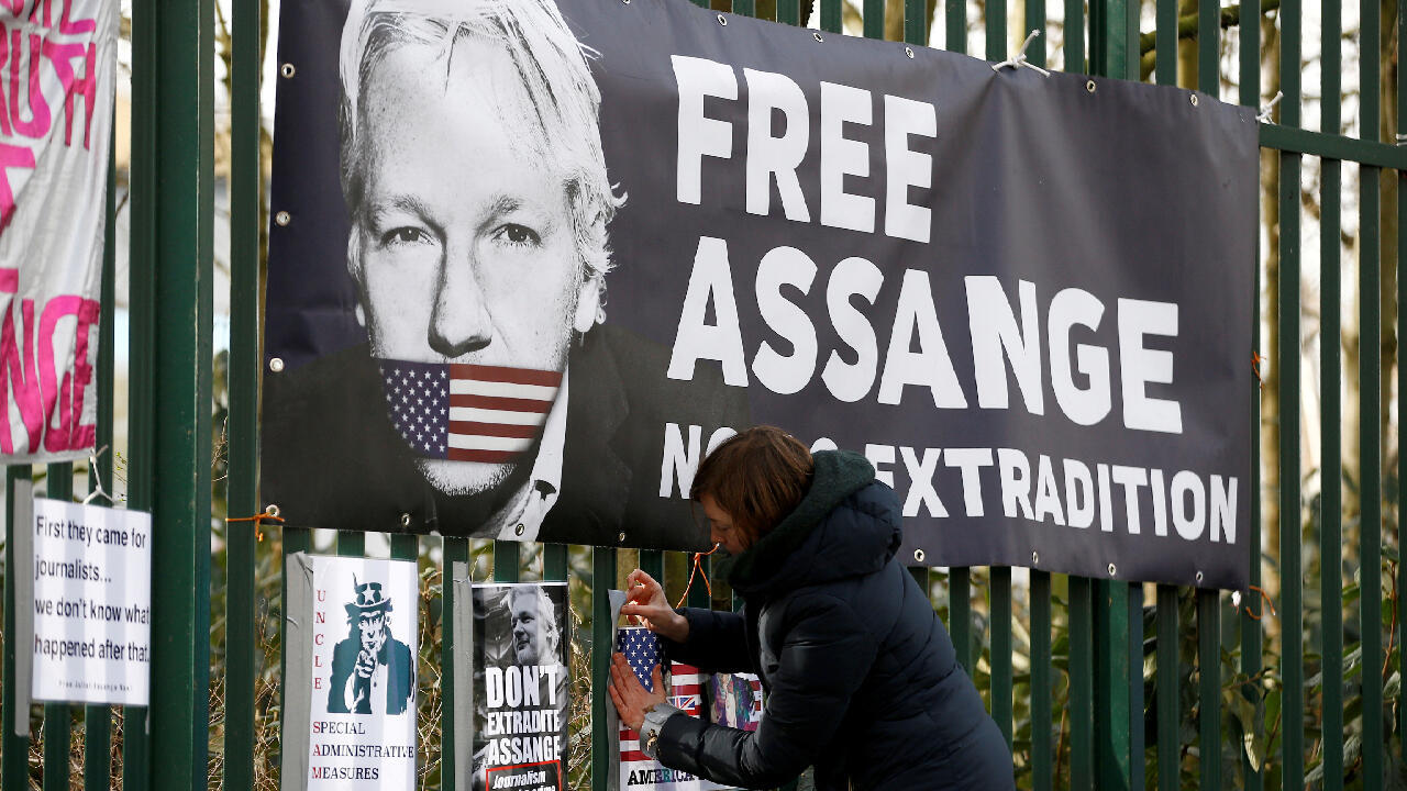 A supporter of Julian Assange posts a poster near the Court where the hearings on the possible extradition of the founder of Wikileaks are progressing, in London, United Kingdom, on February 25, 2020.