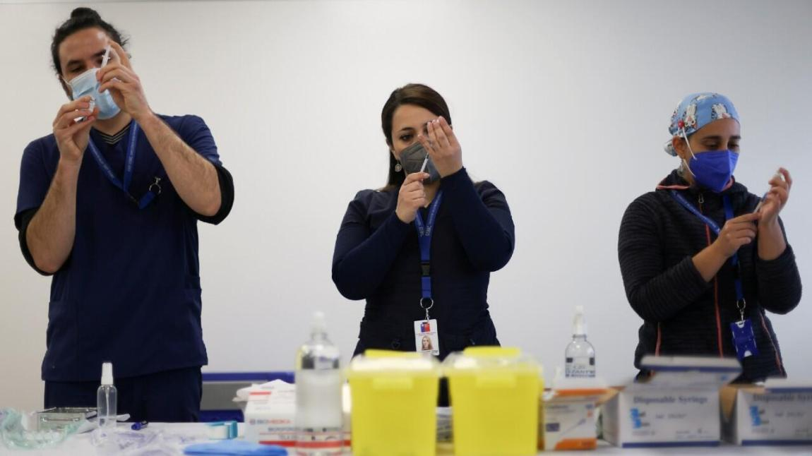 Health workers prepare doses of vaccines against the Pfizer / BioNTech coronavirus disease during a vaccination campaign inside the University of Santiago, Chile June 30, 2021