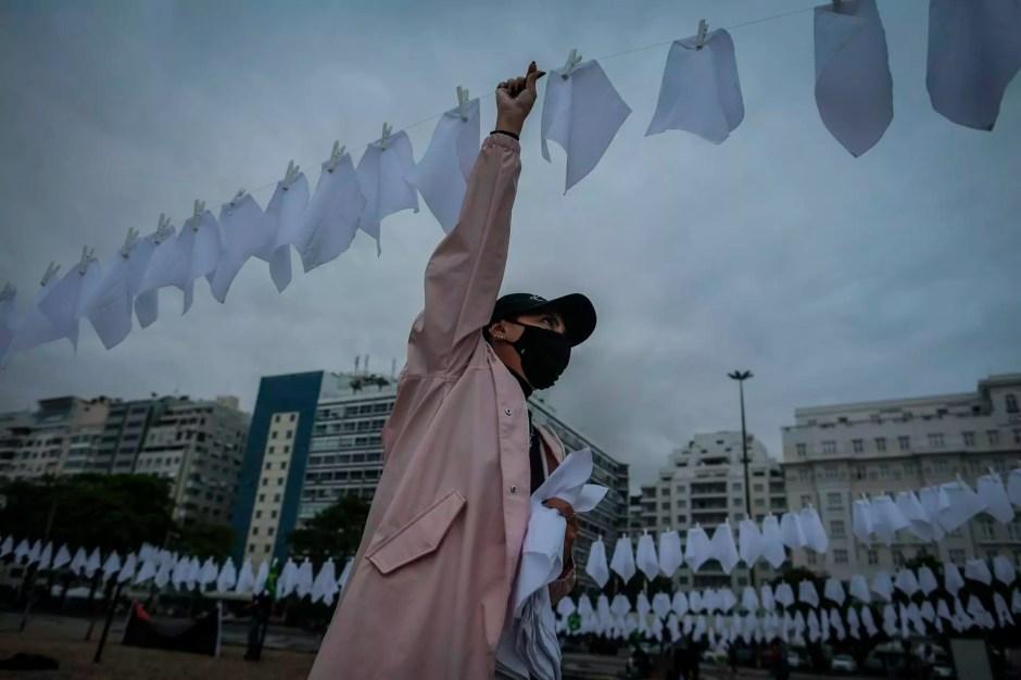 Una voluntaria ayuda a colgar pañuelos blancos durante un homenaje a las miles de víctimas mortales de Covid-19 en Río de Janeiro, Brasil. 8 de octubre de 2021.