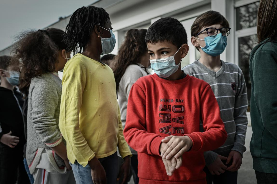 Several children clean their hands with hydroalcoholic gel before a saliva sample is taken for a coronavirus test, on February 25, 2021, at a school in Eysines, outside the French city of Bordeaux.