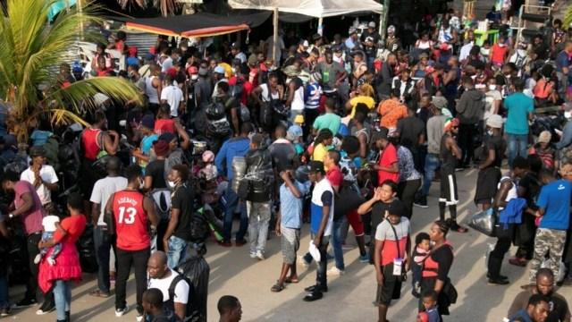 Los migrantes se reúnen junto a las tiendas mientras esperan cruzar a Panamá para continuar su viaje hacia los EE. UU., En Necoclí, Colombia, el 5 de agosto de 2021.