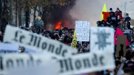 Personas con pancartas y carteles asisten a una manifestación contra la 'ley de seguridad global' en París, el 28 de noviembre de 2020.