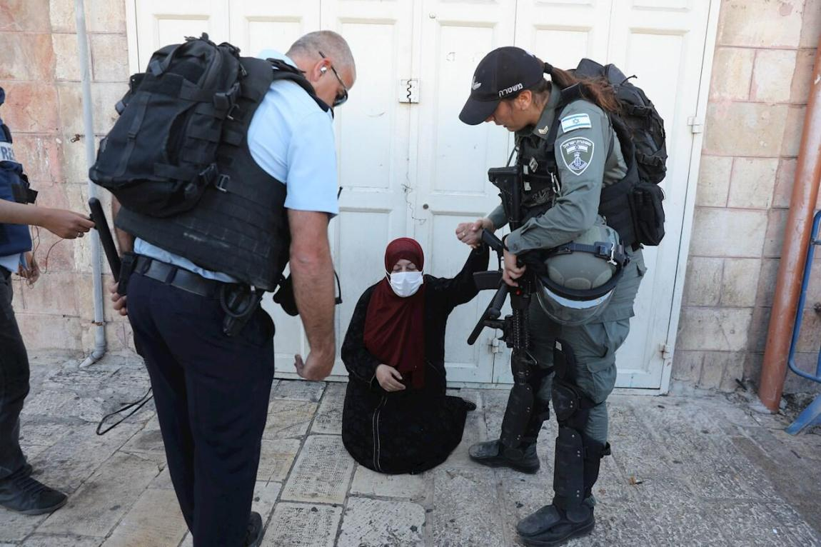 Israeli police forces ask a Palestinian woman to leave the area near the Damascus Gate during the March of the Flags in the old city of Jerusalem, June 15, 2021. The March of the Flags continued despite threats from the Palestinian militant organization Hamas, which called on Israel to cancel the march through the Old City of Jerusalem.