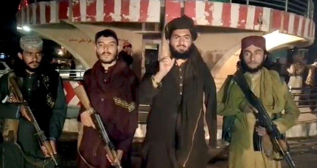 Taliban fighters record a message after taking over Pul-e-Khumri, capital of Baghlan province, Afghanistan, in this still image taken from a social media video.