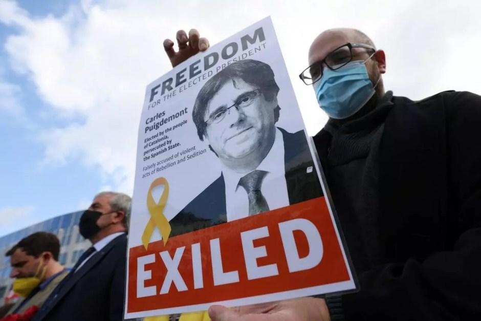 Una persona sostiene un cartel con la imagen del expresidente del Gobierno catalán Carles Puigdemont, que ha sido detenido en Cerdeña, durante una protesta en su apoyo frente al Parlamento Europeo, en Bruselas, Bélgica, el 24 de septiembre de 2021.
