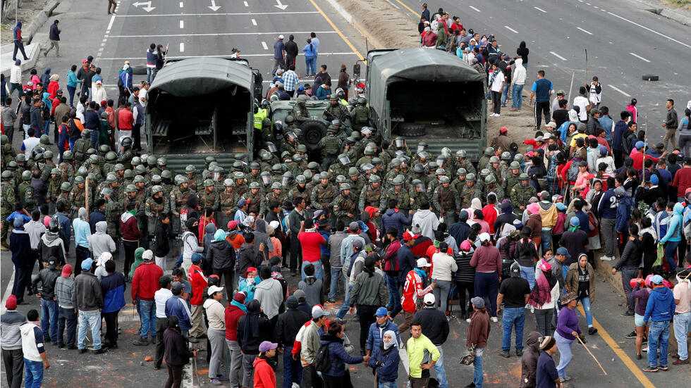 Un grupo de manifestantes rodea a los militares mientras bloquean una carretera en medio de las protestas contra las recientes medidas del Gobierno, en Lasso, Ecuador, el 6 de octubre de 2019. Enérgica condena del FMLN a represión policial en Ecuador-VerdadDigital.com-