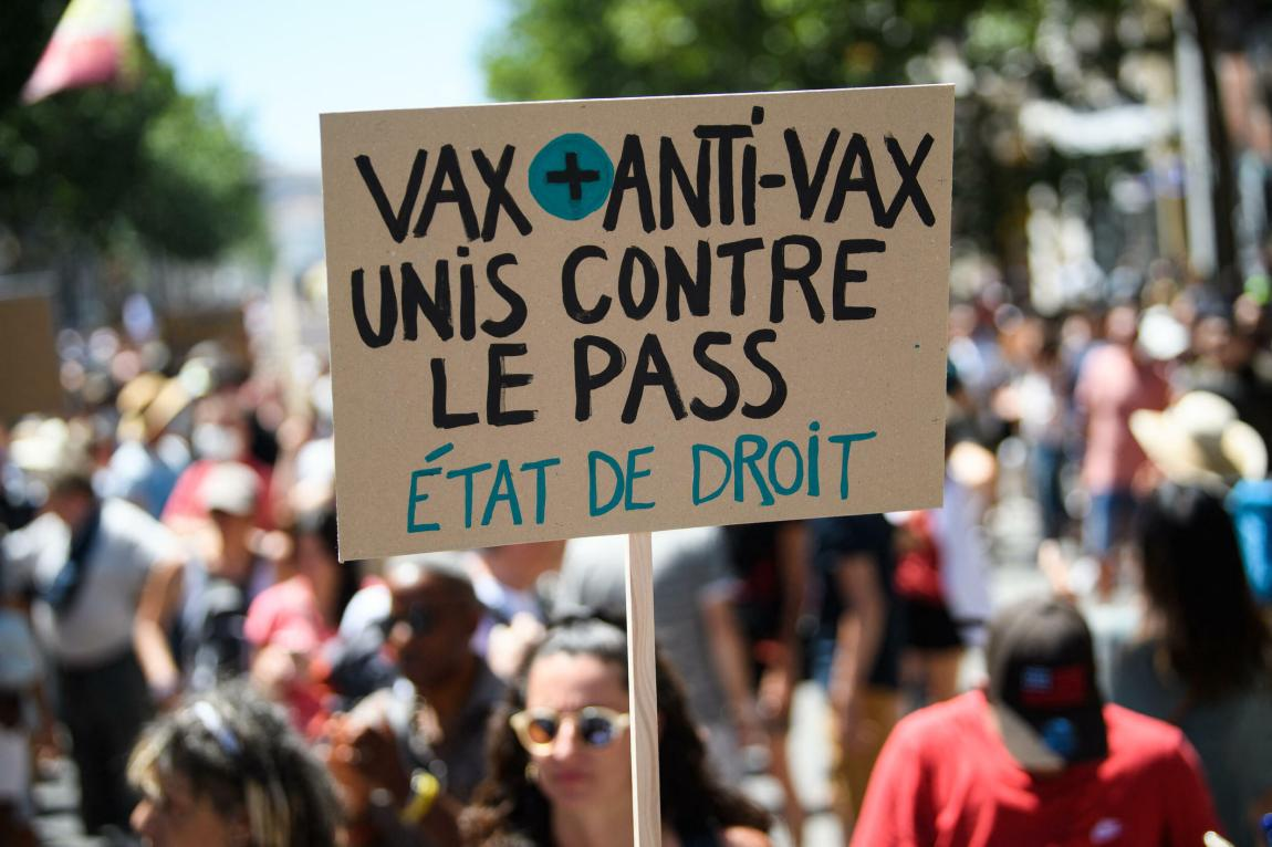 """A protester holds a banner """"Vax and anti-vax united against the pass.  Rule of law"""" during a demonstration in Marseille on July 17, 2021, against the new sanitary restrictions in France."""