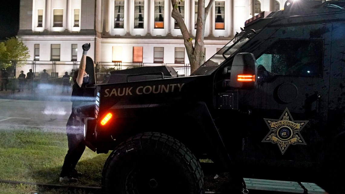 A protester obstructs an armored vehicle attempting to clear the park of demonstrators during clashes outside the Kenosha County Courthouse late Tuesday, Aug. 25, 2020, in Kenosha, Wis. Protests have erupted following the police shooting of Jacob Blake two days earlier. (AP Photo/David Goldman)