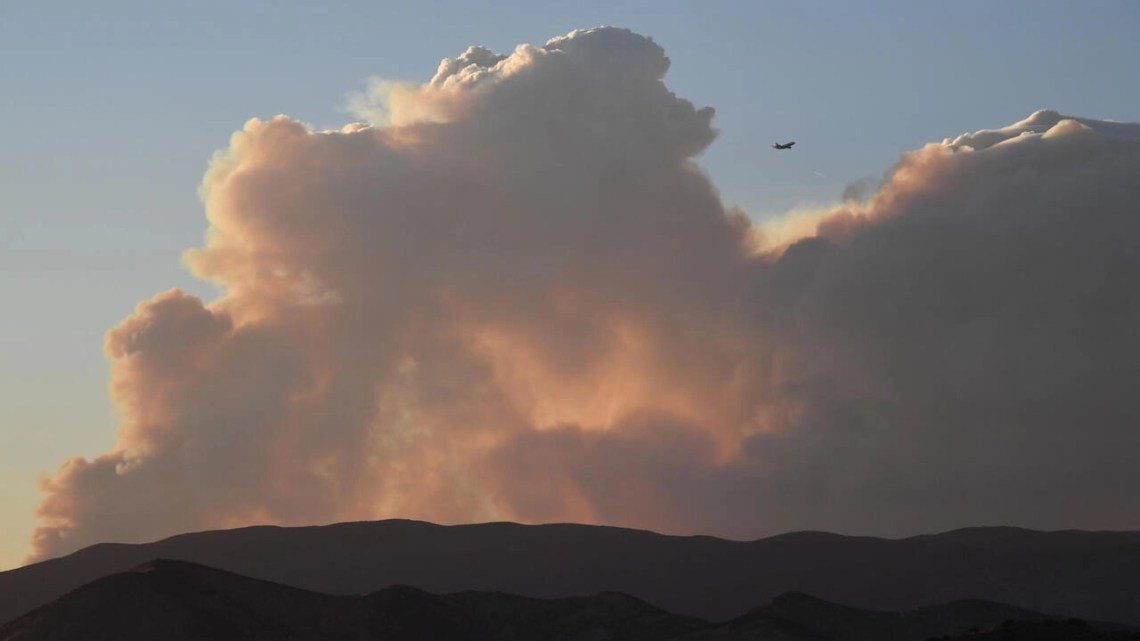 A plane flies past smoke from the Lake Fire in the Angeles National Forest