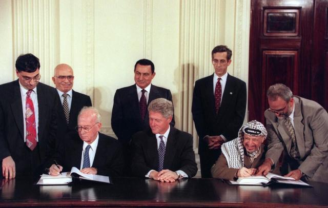 US President Bill Clinton watches Israeli Prime Minister Yitzhak Rabin and PLO Chairman Yasser Arafat sign a peace accord in the White House as Hosni Mubarak and King Hussein of Jordan look on in September 1995.