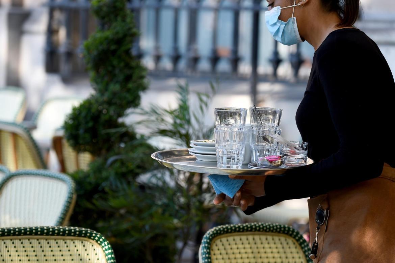 A waitress wears a mask at the Café des Phares on place de la Bastille.