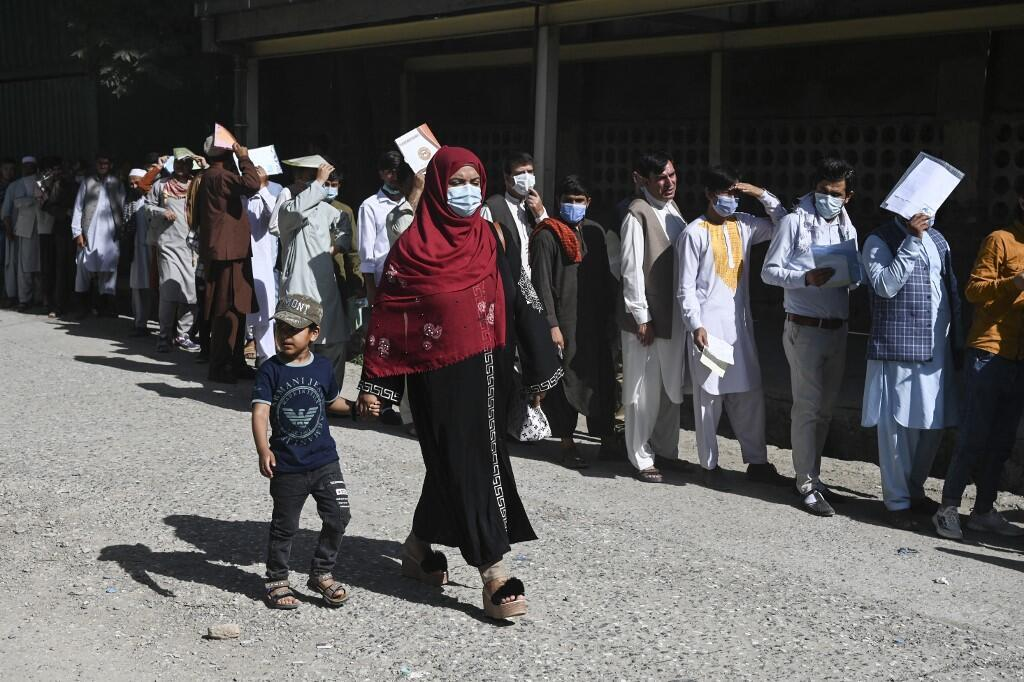 A woman with a child walks past people queuing to submit their passport applications at an office in Kabul on July 25, 2021.
