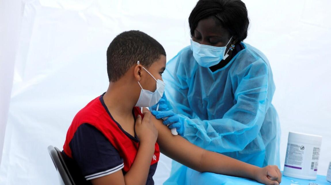 Justing, 12, receives a dose of the Pfizer-BioNTech vaccine against Covid-19 disease during a vaccination event for local teens and adults outside the Bronx Writing Academy school in Bronx County.  from New York City, New York, USA, on June 4, 2021.