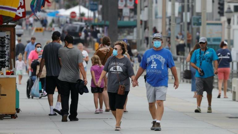 File-Dozens of people wearing masks walk along the oceanic pier, while the United States passed the barrier of 4 million infections on Thursday, by Covid-19.  In Huntington Beach, California, United States, on July 23, 2020.