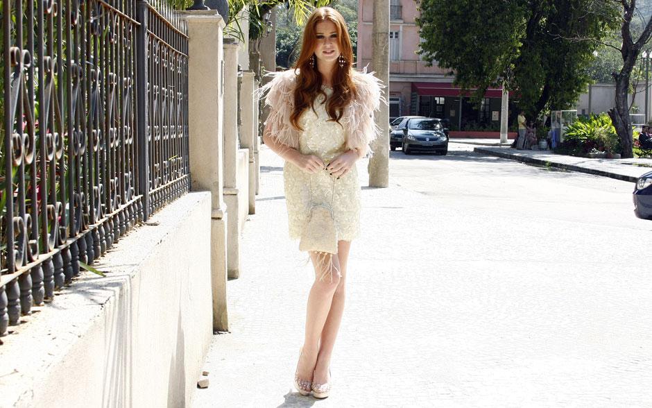 Alice, em tom pastel no vestido brilhoso e cheio de plumas