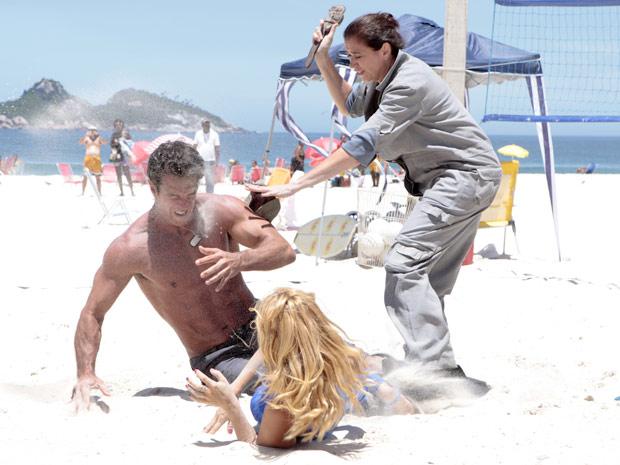 A loira joga areia nos olhos do grandalhão (Foto: Fina Estampa/TV Globo)