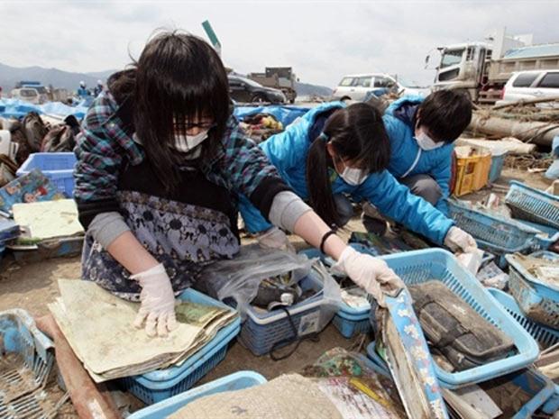 Crianças procuram por seus pertences em escombros de escola em região devastada de Ishinomaki, cidade da província de Miyagi  (Foto: AFP)