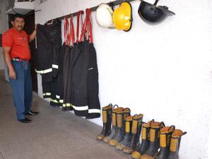 Equipamentos de proteção, que deveriam ser de uso individual, ficam pendurados em parede e são de uso coletivo. Há falta de trajes (Foto: Renato Bezerra/G1)