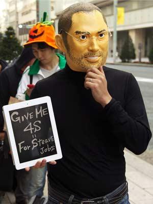 Homem usa máscara do fundador da Apple, Stevie Jobs, em fila no Japão. (Foto: Kim Kyung-Hoon/Reuters)
