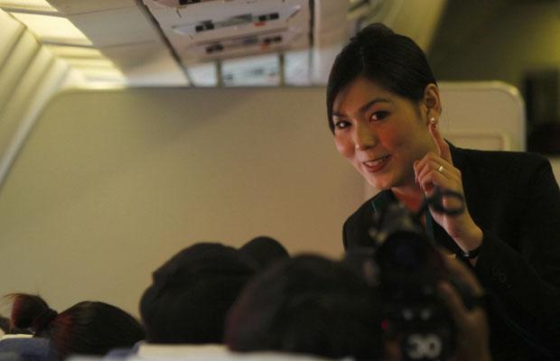 Nathatai Sukkaset, de 26 anos, conversa com passageiros durante o voo nesta quinta-feira (15)  (Foto: Reuters)