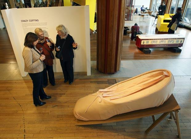 Visitantes de exposição em Londres observam caixão no formato de sapatilha de balé. (Foto: Justin Tallis/AFP)