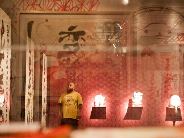 Felipe Yung, o Flip, posa ao lado de suas obras de arte (Foto: Caio Kenji/G1)