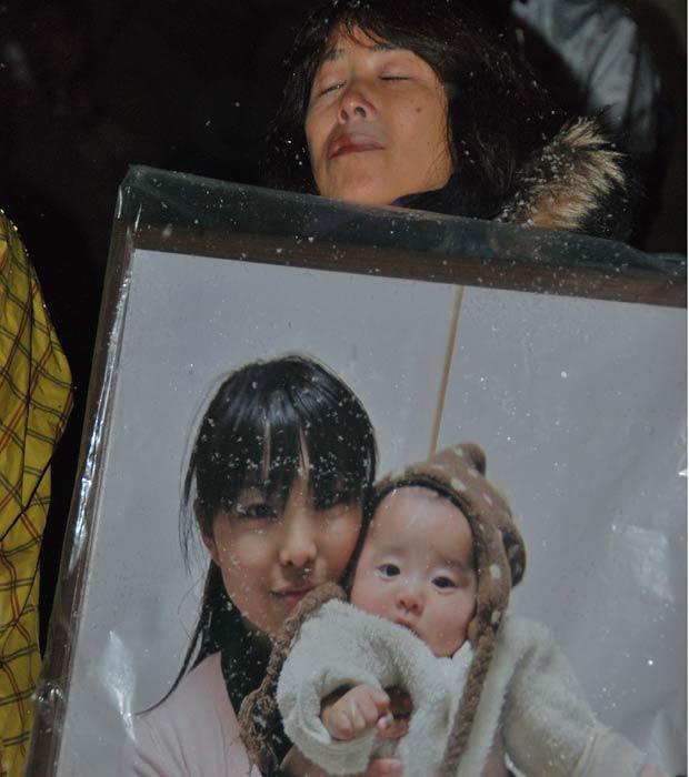 Japonesa segura o retrato da filha e do neto de seis meses mortos no tsunami. Ela participou da homenagem às vítimas em uma queima de fogos na montanha de  Izumigaoka, em Sendai, a maior cidade atingida pelo tsunami. (Foto: Roberto Kovalick/TV Globo)