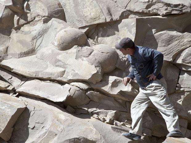 Homem observa ossos de dinossauros fossilizados na região da Chechênia (Foto: Reuters/Yelena Fitkulina)
