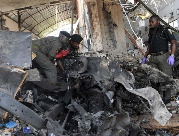 Policiais no local da explosão de carro bomba nesta quinta-feira (26) em Abuja, na Nigéria (Foto: AFP)