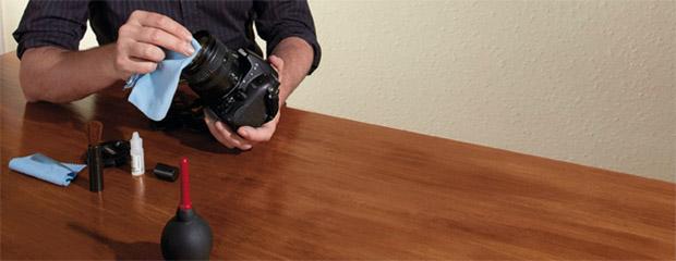 Kit de limpeza sobre mesa e fotógrafo limpando parte frontal da lente com lenço de microfibra (Foto: Reprodução/Digital Camera World)