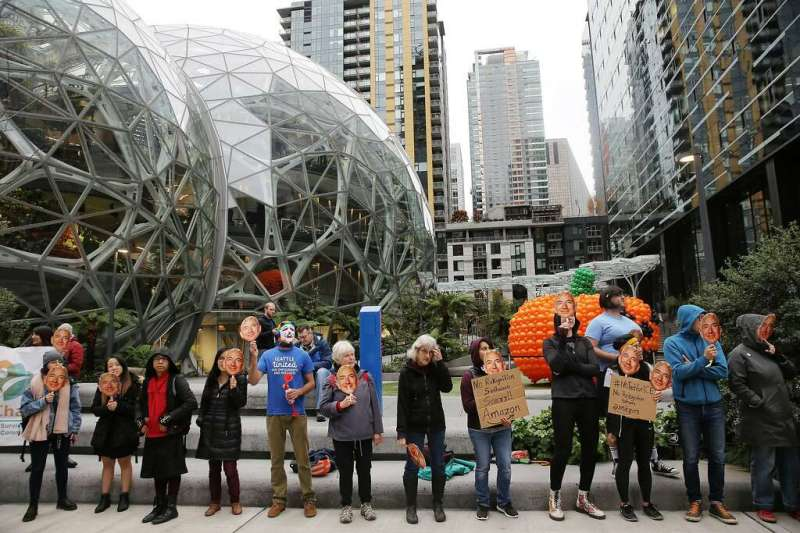 """Several dozen protesters hold up Jeff Bezos masks as they gather downtown to denounce Amazon for providing their facial recognition software, """"Rekognition,"""" to the Immigration and Customs Enforcement Agency"""