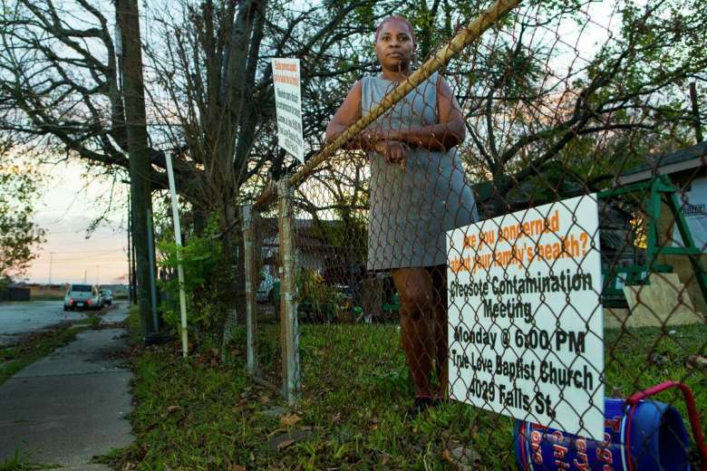 Sandra Edwards stands in the front yard of her home on Thursday, Dec. 5, 2019, in Houston. A cancer cluster was identified in the the historically black north Houston neighborhoods of the Fifth Ward and Kashmere Gardens, near a site of legacy contamination from rail yard operations. Creosote was used for decades to treat wooden railroad ties in the yard. Though wood treatment has ceased for many years, the creosote sunk deep into the ground, creating a plume that has moved beneath an estimated 110 properties.