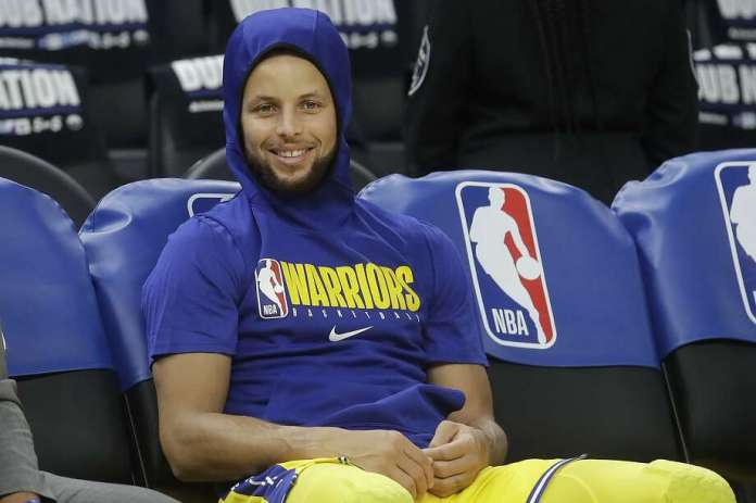 Golden State Warriors goalkeeper Stephen Curry smiles on the bench as players warm up before an NBA basketball game between the Warriors and the Los Angeles Lakers in San Francisco on Thursday, February 27, 2020. (AP Photo / Jeff Chiu) Photo: Jeff Chiu / Associated Press