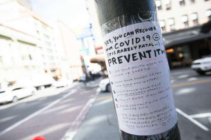 A handmade sign on Grant Ave. in San Francisco, California, March 10, 2020, explains how to contain the COVID-19 coronavirus. The streets of San Francisco were significantly quieter because of the coronavirus, which prompted many workers to encourage workers to stay at home. Photo: Douglas Zimmerman / SFGate.com