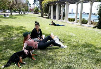 Sammy Consani and Nutella (left) sit with Hannah Suh on Lake Merritt in Oakland on May 16, 2020. Oakland city officials strongly discourage meetings on the lake and in the park and remind people to keep a social distance as long as the corona virus shelter is placed in order .