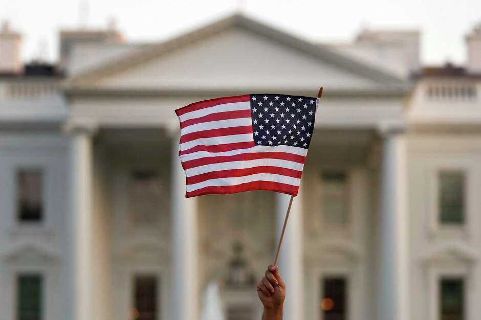 A flag is waved outside the White House in 2017. The Trump administration's moves to limit H-1B visas will have an immediate economic impact in Texas, delivering a blow to critical industries such as health care, finance and IT that are already reeling from the effects of the ongoing COVID-19 pandemic.