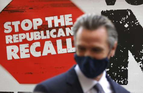 """A sign against the recall is posted behind California Gov. Gavin Newsom as he talks with volunteers who are phone banking against the recall at Manny's on Aug. 13, 2021, in San Francisco. California Gov. Gavin Newsom kicked off his """"Say No"""" to recall campaign as he prepares to face a recall election on Sept. 14."""