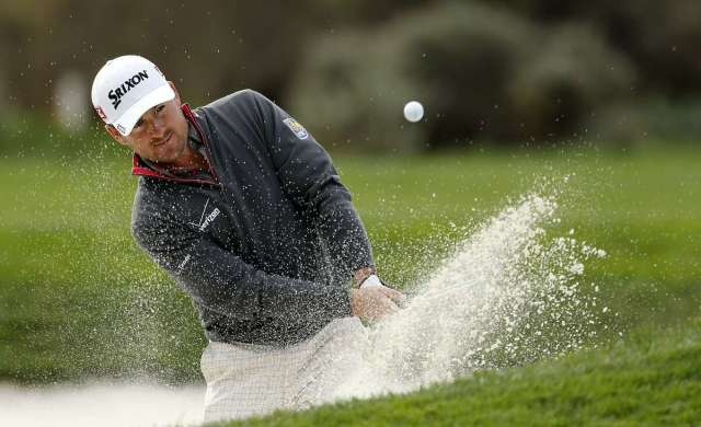 Graeme McDowell hits a sand shot on the par-3 12th hole at Pebble Beach during practice rounds on Tuesday Feb. 4, 2014, before the start of the Pebble Beach National Pro-Am golf tournament in Pebble Beach, Calif.