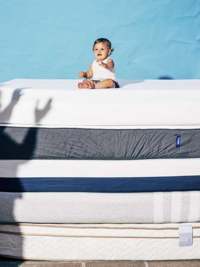 A Baby Sits Atop Mattresses From Several Companies That Were The Subjects Of In Home