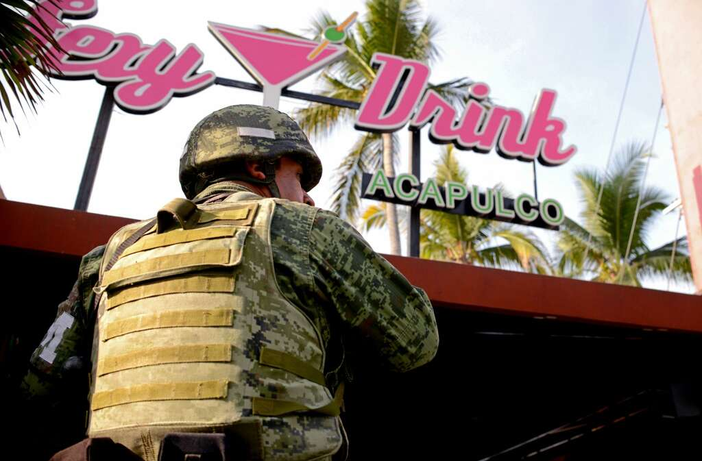 A soldier of the Mexican Army stands in front of Baby Lobster and Sexy Drink bars after an evening shoot-out were several people were wounded by firearms at the touristic neighborhood of Condesa in Acapulco resort, Guerrero State, Mexico on January 28, 2018.  / AFP PHOTO / FRANCISCO ROBLES        (Photo credit should read FRANCISCO ROBLES/AFP/Getty Images) Photo: FRANCISCO ROBLES/AFP/Getty Images