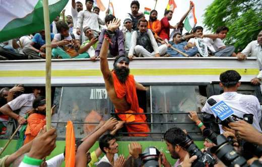 Indian yoga guru Baba Ramdev waves out of the window of a bus after he was detained with his supporters by policemen in New Delhi in 2012. The New Indian Express reported Sunday that the prominent yogi will deliver the inaugural address of the 7th annual Translational Cancer Research Conference, which starts Thursday in India.  Photo: Saurabh Das, Associated Press / AP