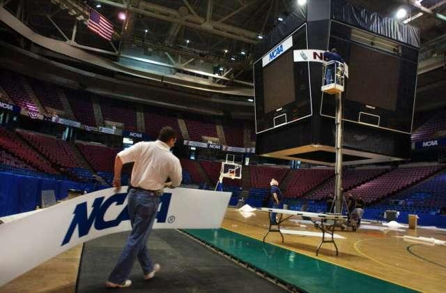 Pepsi Arena operations director Doug McClaine carries an NCAA sign to replace a Nextel sign in the scoreboard at the Pepsi Arena in Albany March 26, 2003, in preparation for this weekend's NCAA East Regional final in men's basketball. Pepsi employee Tom Mink stands in a lift replacing the signs, while Bob Kirkpatrick, second from left, helps out. The scoreboard normally is raised near the rafters of the arena during events.